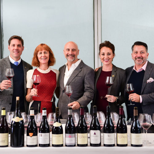 Board and Panel line up for Pinot Talks with a glass of wine